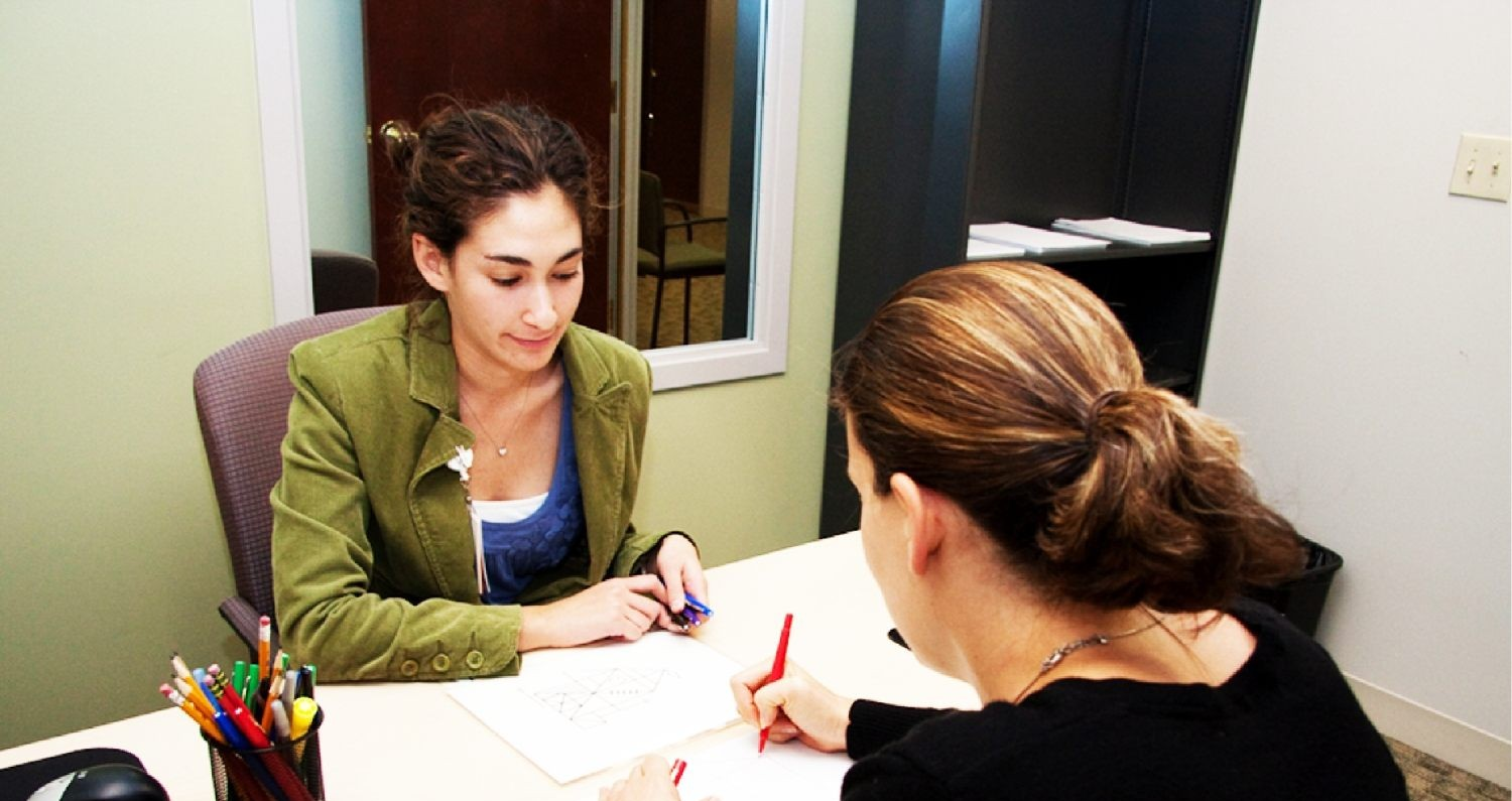A woman signing a document with another woman.
